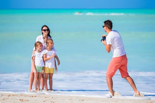 Família de quatro pessoas tirando uma foto de selfie em suas férias de praia. férias na praia da família