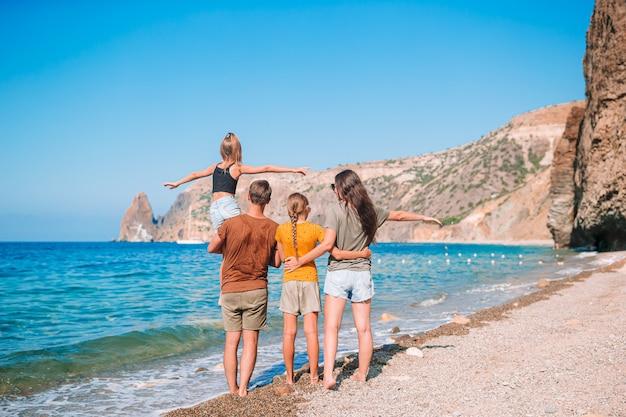 Família de quatro se divertindo juntos na praia