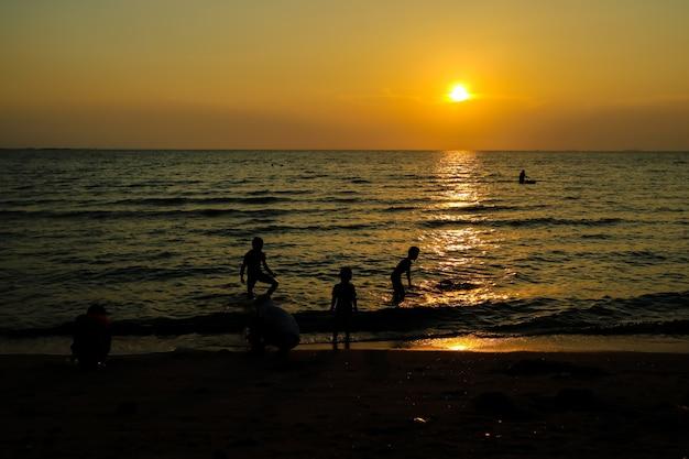 Família de silhueta e animal de estimação na praia e mar areia pôr do sol