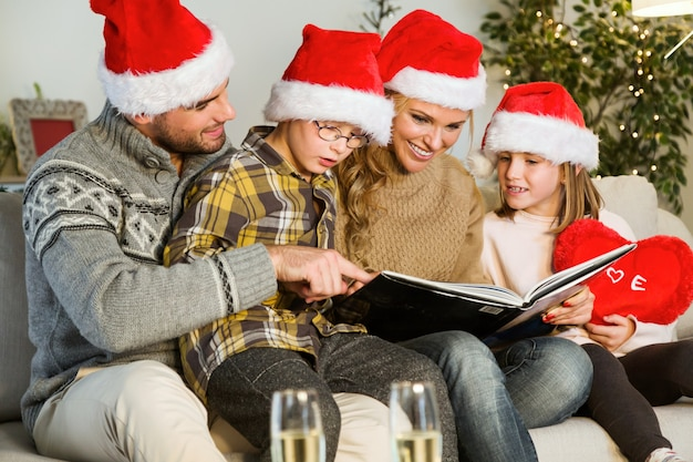 Família de sorriso com chapéus de papai noel e olhando um álbum de fotos
