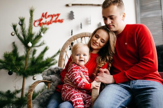 Família de sorriso feliz no estúdio no fundo da árvore de natal com presente