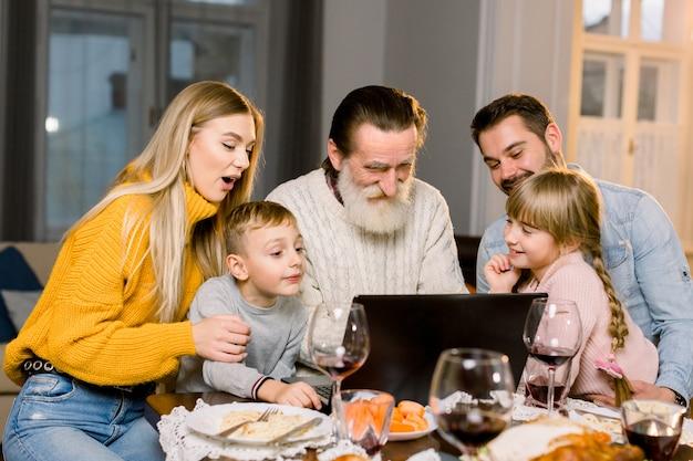 Família de sorriso feliz que olha o filme ou que faz a ligação através do internet usando o portátil, sentando-se no tabe festivo em casa, comemorando o jantar junto. dia de ação de graças conceito