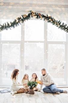 Família de suéteres brancos sentada no chão
