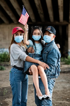 Família de tiro médio com bandeira e máscara facial
