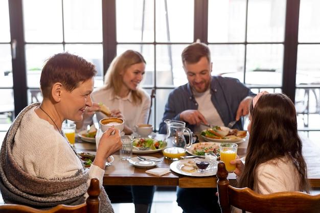 Família de tiro médio comendo junta à mesa