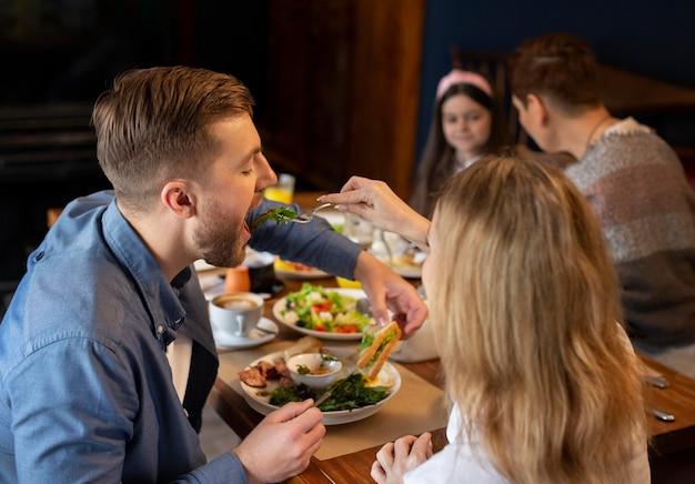 Família de tiro médio comendo junta