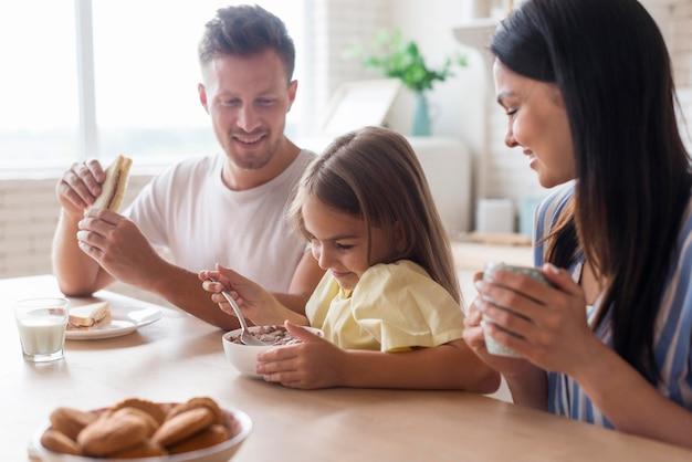 Família de tiro médio comendo juntos