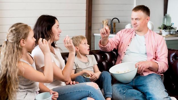 Família de tiro médio comendo pipoca