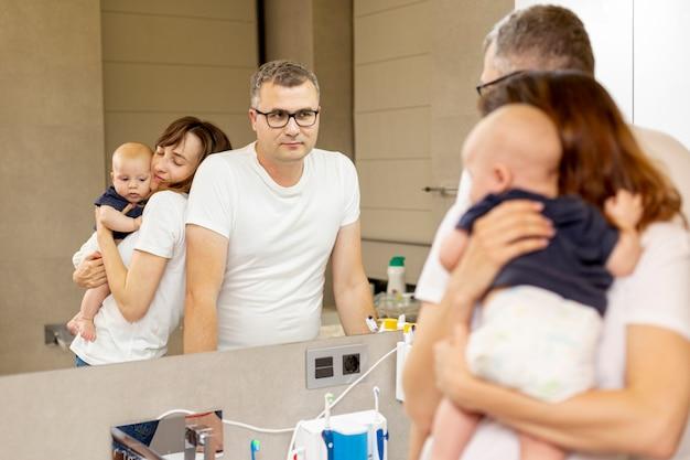 Família de tiro médio, olhando no espelho