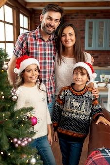 Família de tiro médio posando juntos dentro de casa