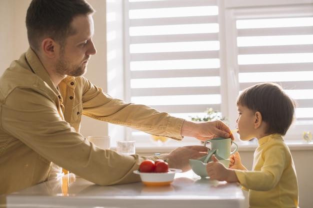 Família de tiro médio tomando café da manhã na cozinha