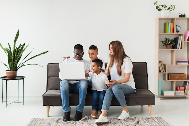 Família de tiro no escuro, olhando em um laptop