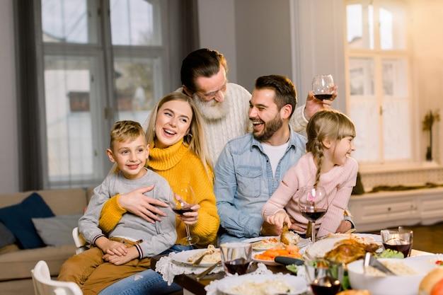 Família de três gerações, jantar juntos em casa na sala de estar