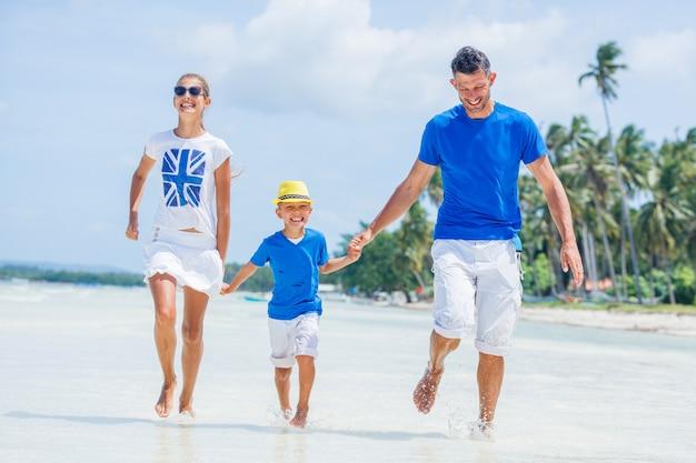 Família de três - pai com filho se divertindo na praia