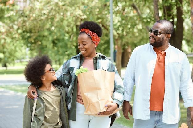 Família de três pessoas caminhando pelo parque enquanto voltava do supermercado