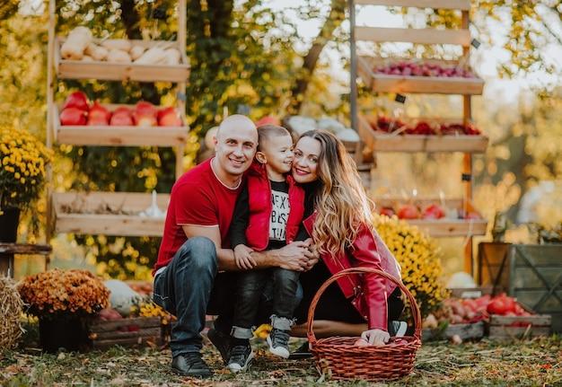 Família de três pessoas com mãe grávida posando em um mercado aberto