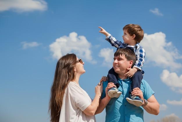 Família de três pessoas, pais jovens e um filho pequeno em um fundo de céu