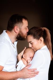 Família de três pessoas segurando um bebê recém-nascido, se abraçando e se beijando em fundo escuro