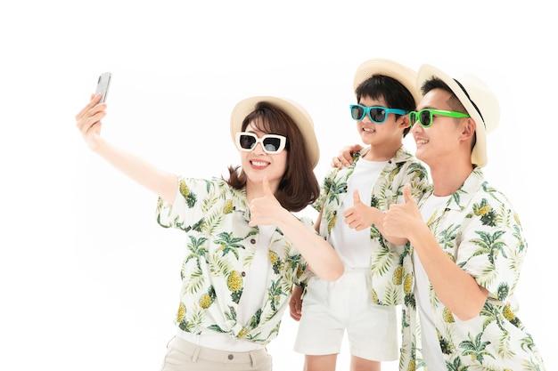 Família de três viajando tomando uma selfie