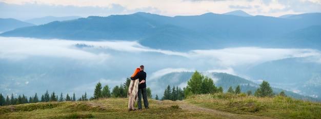 Família de turista - homem e mulher em pé em uma colina, desfrutando de uma manhã de neblina sobre as montanhas
