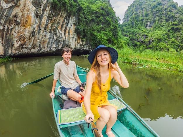 Família de turistas felizes em um barco no lago tam coc ninh binh vietnã é patrimônio mundial da unesco