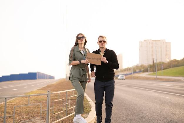 Família de um jovem casal de caronas na rodovia esperando o carro para viajar pela liberdade com amor