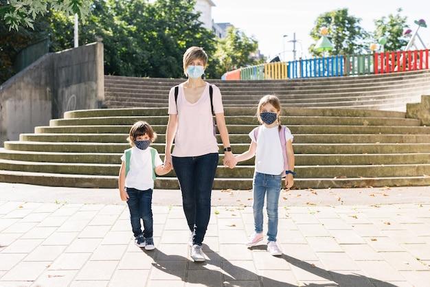 Família de uma mãe com seus dois filhos caucasianos indo para a escola no início do ano letivo usando máscaras por causa da covid19 pandemia de coronavírus