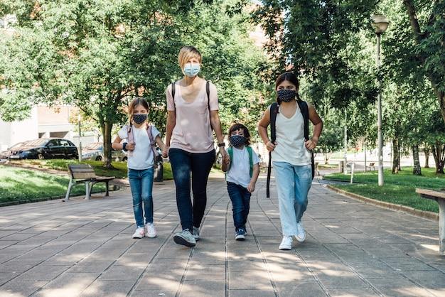 Família de uma mãe com seus três filhos caucasianos indo para a escola no início do ano letivo usando máscaras por causa da covid19 pandemia de coronavírus
