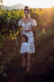 Família de uma mãe em um vestido com seu filho caminhando por um vinhedo no verão na itália