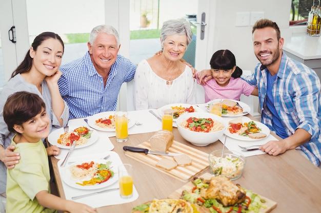 Família de várias gerações a sorrir na mesa de jantar