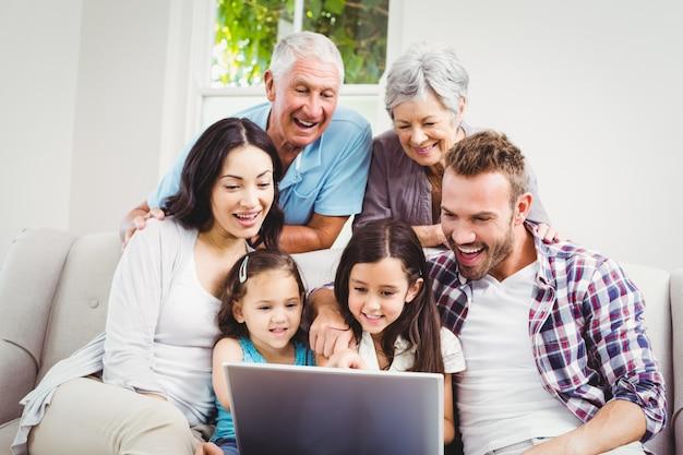 Família de várias gerações a sorrir usando um laptop