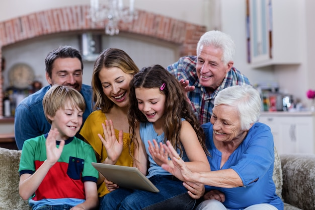 Família de várias gerações, agitando as mãos enquanto usa o tablet digital para bate-papo por vídeo