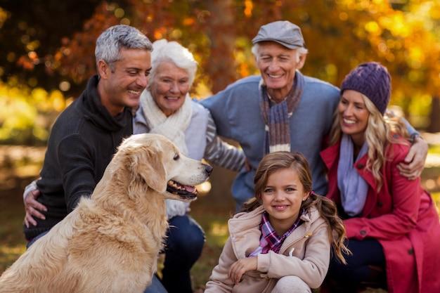 Família de várias gerações alegre com cachorro no parque
