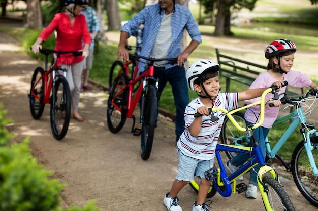 Família de várias gerações, andando com bicicleta no parque
