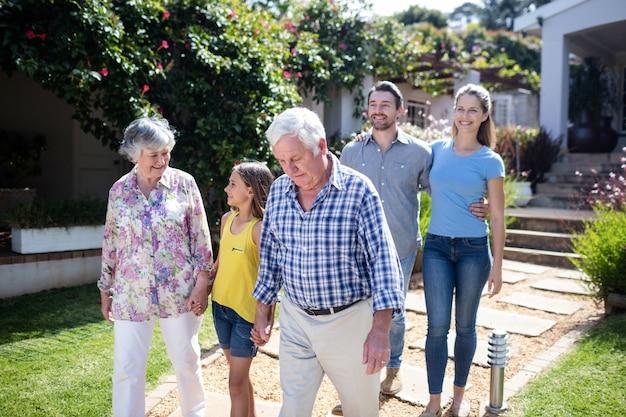 Família de várias gerações, andando no caminho do jardim