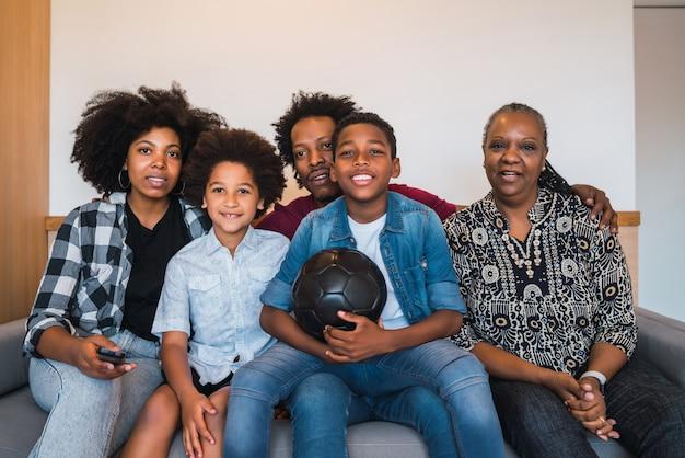 Família de várias gerações, assistindo a partida de futebol em casa.