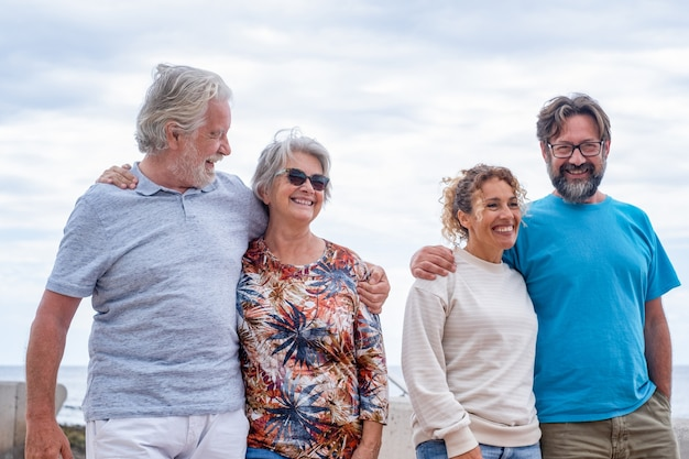 Família de várias gerações caminhando junta ao ar livre, sorrindo despreocupada