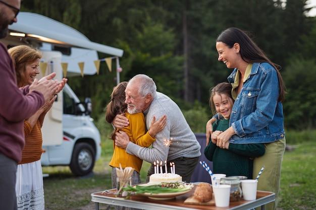 Família de várias gerações comemorando aniversário ao ar livre no acampamento, viagem de férias em caravana.