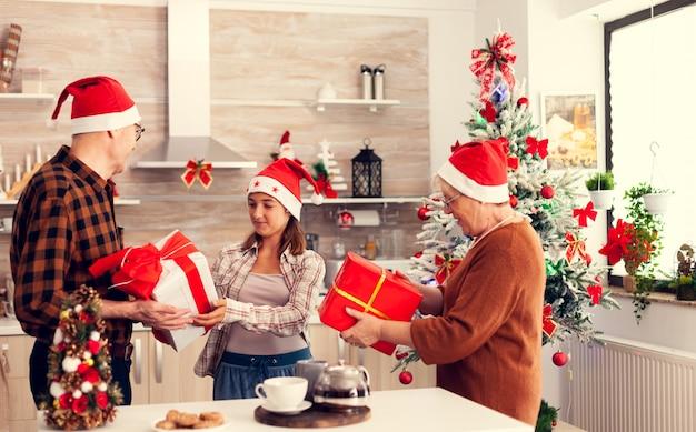 Família de várias gerações comemorando o natal com caixas de presente