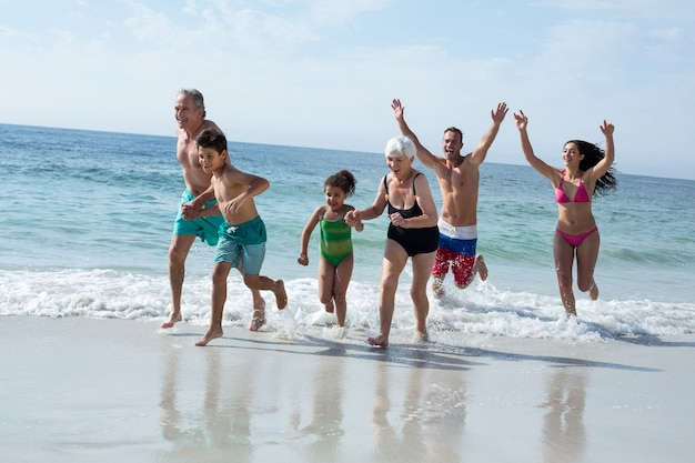 Família de várias gerações correndo na praia