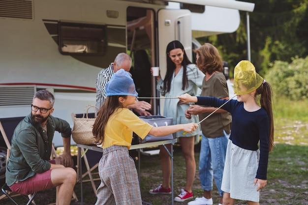 Família de várias gerações desfazendo as malas e conversando de carro, viagem de férias em caravana.