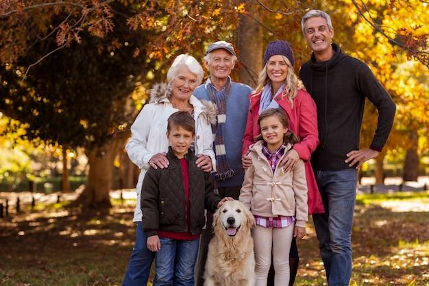 Família de várias gerações em pé com cachorro no parque