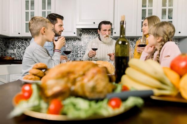 Família de várias gerações, sentada à mesa festiva com peru assado e pratos saborosos