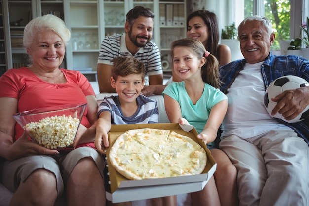 Família de várias gerações, sentada com pipoca e pizza, enquanto assiste a partida de futebol