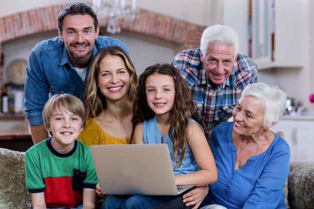 Família de várias gerações, sentada no sofá e usando o laptop
