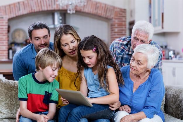 Família de várias gerações, sentada no sofá e usando tablet digital
