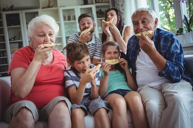 Família de várias gerações, tendo pizza juntos