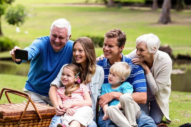 Família de várias gerações, tirando uma selfie no parque