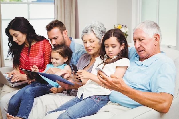 Família de várias gerações usando dispositivos tecnológicos