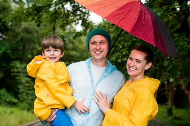 Família de vista frontal sorrindo sob seu guarda-chuva